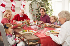 Familie mit den Großeltern, die bei Tisch Weihnachtsmahlzeit genießen Stockfotografie