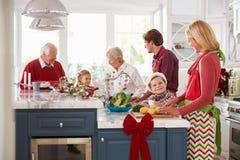 Familie mit den Großeltern, die Weihnachtsmahlzeit in der Küche vorbereiten Stockfotografie