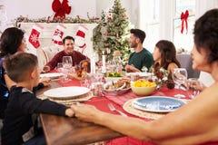 Familie mit den Großeltern, die Grace Before Christmas Meal sagen Stockfoto