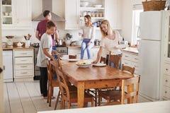 Familie mit den Jugendkindern, die Tabelle für Mahlzeit in der Küche legen stockfotos