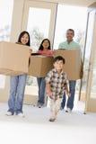 Familie mit den Kästen, die in neues Haus sich bewegen Stockfoto