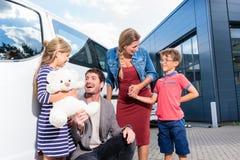 Familie mit den Kindern, die Auto am Autohändler kaufen Lizenzfreies Stockbild