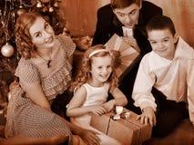 Familie mit den Kindern, die Geschenke empfangen. Lizenzfreie Stockbilder