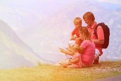 Familie mit den Kindern, die herein Kartenreise betrachten Lizenzfreie Stockfotografie