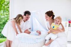 Familie mit den Kindern, die mit neugeborenem Baby spielen Stockfoto