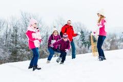 Familie mit den Kindern, die Schneeballkampf im Winter haben Stockfotografie