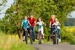 Familie mit den Kindern, die in Sommer mit Fahrrädern radfahren Lizenzfreie Stockfotos