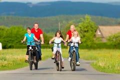 Familie mit den Kindern, die in Sommer mit Fahrrädern radfahren Lizenzfreies Stockbild