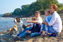 Familie mit den Kindern und Hund, die auf dem Strand stillstehen Stockbild