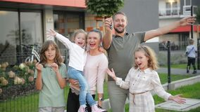 Familie mit den Kindern, welche die Kamera draußen steht auf Straße betrachten Paare und Kinder, die neues Haus kaufen Real Estat stock footage