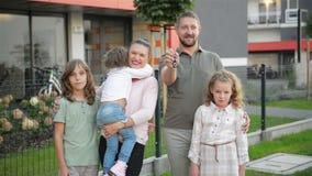 Familie mit den Kindern, welche die Kamera drau?en steht auf Stra?e betrachten Paare und Kinder, die neues Haus kaufen Real Estat stock footage