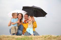 Familie mit den Regenschirmen Stockfotos