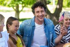 Familie mit der amerikanischen Flagge, die ein Picknick hat Lizenzfreie Stockfotografie