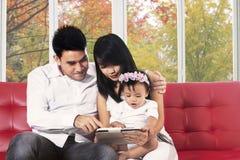Familie mit der digitalen Tablette, die auf Trainer sitzt Stockbild