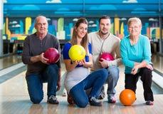Familie mit der multi farbigen Bowlingkugelaufstellung lizenzfreie stockfotos