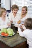 Familie mit drei Erzeugungen in der Küche das Mittagessen essend Stockbilder