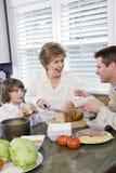 Familie mit drei Erzeugungen in der Küche das Mittagessen essend Lizenzfreie Stockfotografie