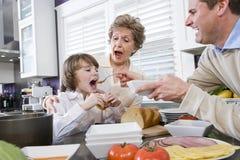 Familie mit drei Erzeugungen in der Küche das Mittagessen essend Stockfoto