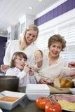 Familie mit drei Erzeugungen in der Küche das Mittagessen essend Stockfotografie