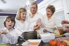 Familie mit drei Erzeugungen in der Küche das Mittagessen essend Stockfotos