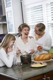 Familie mit drei Erzeugungen in der Küche das Mittagessen kochend Lizenzfreie Stockbilder