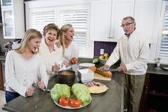 Familie mit drei Erzeugungen in der Küche das Mittagessen kochend Stockfoto