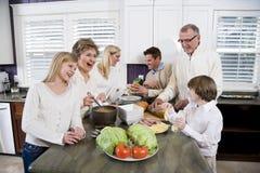 Familie mit drei Erzeugungen in der Küche das Mittagessen kochend Stockfotos