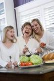 Familie mit drei Erzeugungen in der Küche das Mittagessen kochend Stockbilder