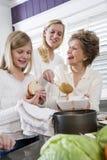 Familie mit drei Erzeugungen zu Hause, die das Mittagessen dient Lizenzfreie Stockbilder