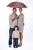 Familie mit einem offenen Regenschirm stockfotografie