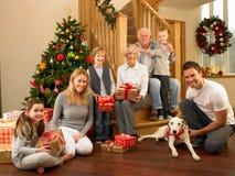 Familie mit Geschenken vor Weihnachtsbaum Stockfotos