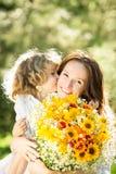 Frau und Kind mit Blumenstrauß der Blumen stockfotografie