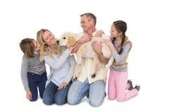 Familie mit ihrem Hund, der zusammen an der Kamera aufwirft und lächelt lizenzfreie stockfotografie