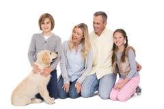 Familie mit ihrem Hund, der zusammen an der Kamera aufwirft und lächelt stockbilder