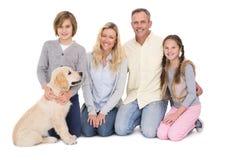 Familie mit ihrem Hund, der zusammen an der Kamera aufwirft und lächelt lizenzfreie stockbilder