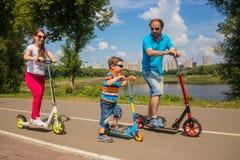 Familie mit jungem Sohnreiten auf Roller Lizenzfreie Stockfotografie