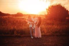 Familie mit Kindern bei Sonnenuntergang stockfotografie