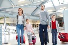 Familie mit Kindern und Koffern im Flughafen stockbilder