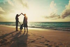 Familie mit Kinderspiel, haben Spaß auf dem Sonnenuntergangstrand und erziehen Lizenzfreie Stockfotos