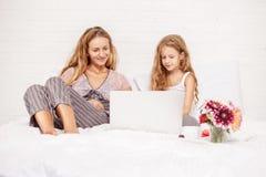 Familie mit Laptop im Bett lizenzfreie stockfotografie