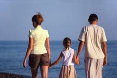 Familie mit Mädchen geht entlang Seestrand. Rückseitige Ansicht. Stockfoto