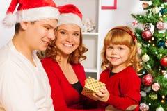 Familie mit offenen Geschenken des kleinen Mädchens auf Weihnachten Stockbild