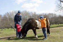 Familie mit Pony Stockfotos