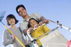 Familie mit Rasenmäher und Gartenarbeitgabel lizenzfreie stockfotos