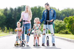 Familie mit Rollern im Park Stockbilder