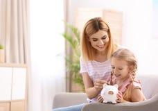Familie mit Sparschwein und Geld zu Hause lizenzfreie stockfotos