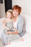 Familie mit Tablet-Computer am Sofa Lizenzfreie Stockbilder