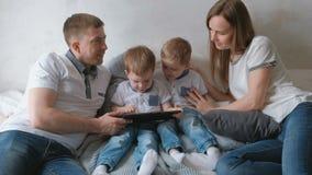 Familie mit Tablette Mutter, Vati und zwei Sohnzwillingskleinkinder, die Karikatur der Tablette liegt auf dem Bett betrachten stock footage