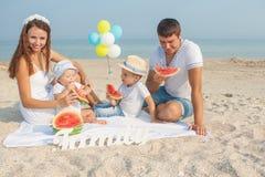 Familie mit Wassermelone auf dem Strand Lizenzfreie Stockfotografie