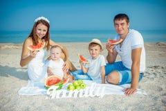 Familie mit Wassermelone auf dem Strand Lizenzfreie Stockbilder